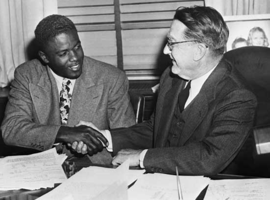 Jackie Robinson and Brooklyn Dodgers general manager Branch Rickey shake hands after agreeing to a contract back in 1948.