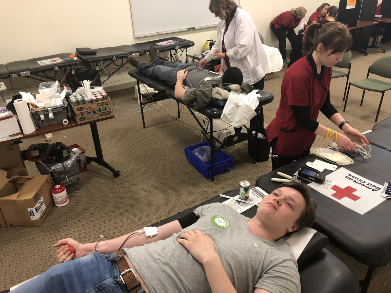 Quinnipiac students donating blood with registered American Red Cross nurses.