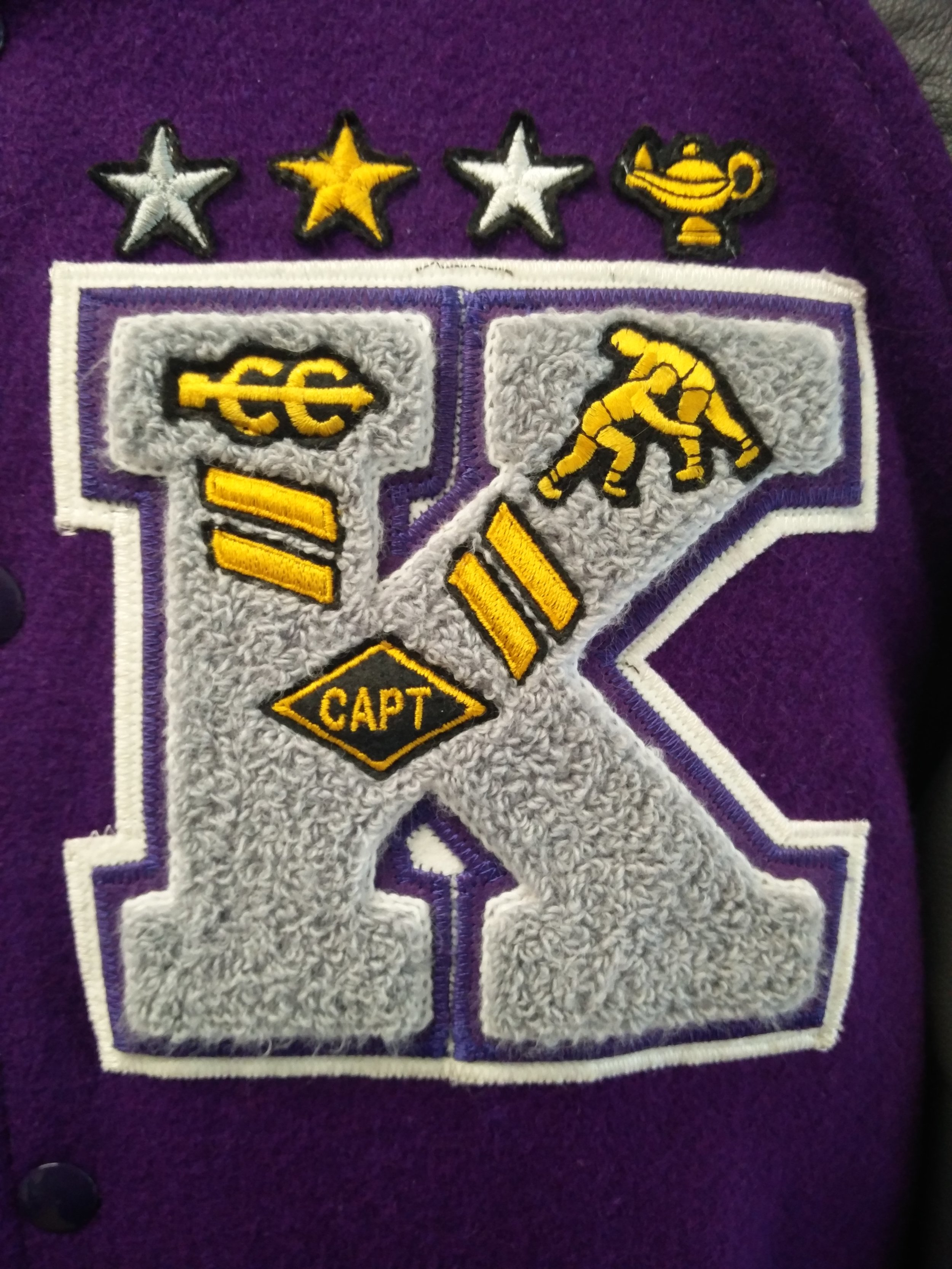 School Letter - The first letter of your school's name. Inlays and corresponding bars are placed on and around it to indicate programs you have lettered in