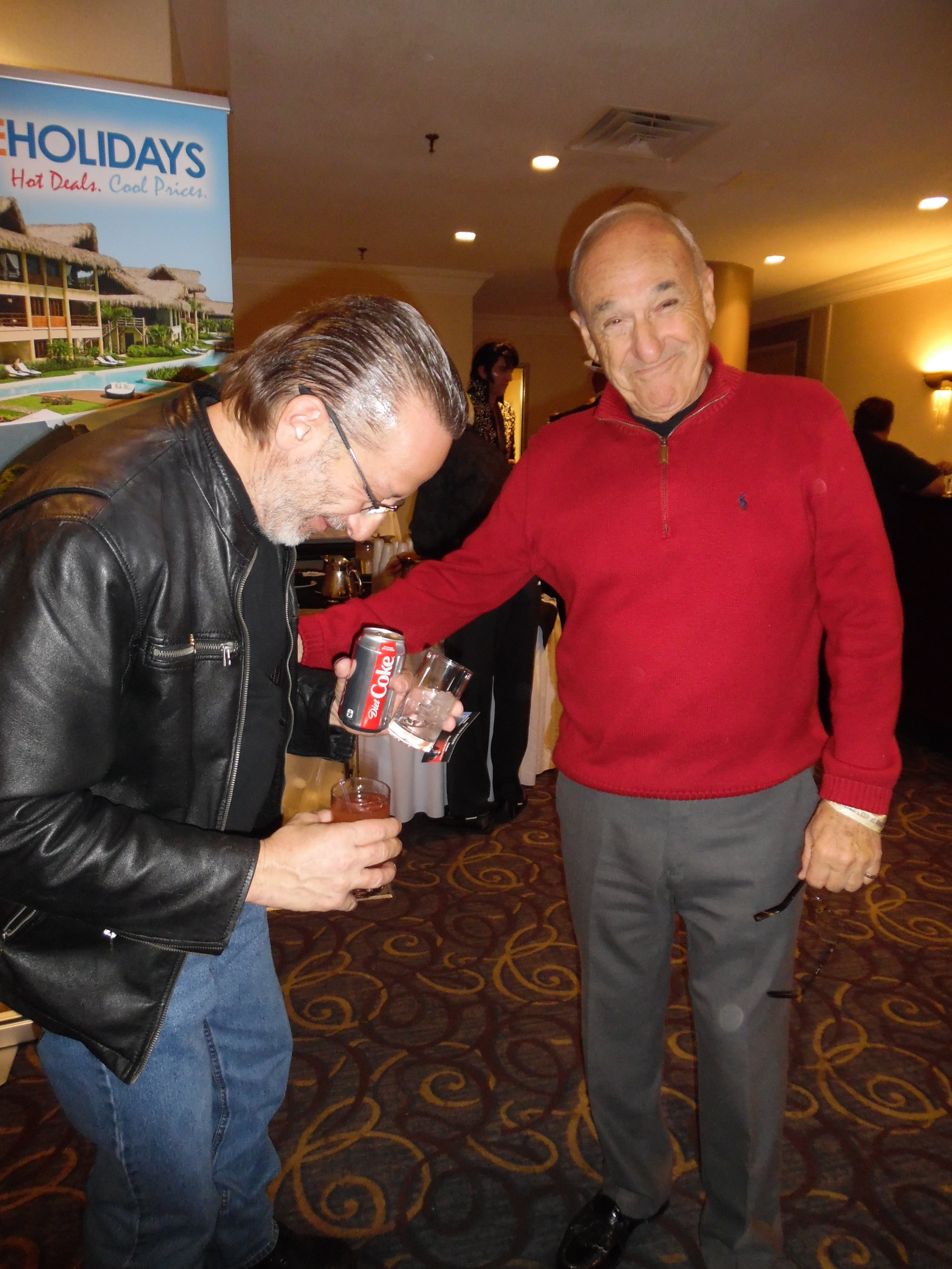 """At the Flaming Star Elvis Festival in 2018, I asked if I might take a photo of Tony with Theo and jokingly added that I knew """"more about him than anyone else"""". Theo found this exchange very amusing…lol.  Photo Credit: C. MacArthur.."""