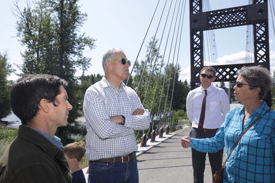 Photo by Ryan Bell Washington Gov. Jay Inslee chatted with Winthrop Mayor Sally Ranzau at the Spring Creek Bridge, as Twisp Town Council member Hans Smith looked on. Inslee also visited Twisp and Pateros on Friday (July 19).