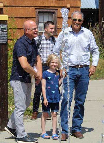 Photo by Don Nelson  TwispWorks Executive Director Don Linnertz, left, chatted with Gov. Jay Inslee as the governor's granddaughter contemplated a dash through the splash pad. Behind them is Inslee staffer Blake Baldwin.