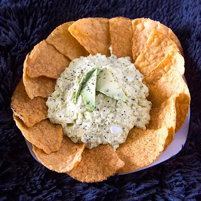 "EASY halloween party food idea! 🎃Spooky avocado egg salad with sweet potato tortilla chips. This is a great option for an office party since it's more filling like a meal, but would also work well for a house party! This high-protein, lower carb and gluten-free recipe is a healthier party food to balance out the table likely filled with sugary desserts and candy. 🍬🍫 To make, I simply substituted half the amount of mayo called-for in my staple egg salad recipe with mashed avocado. You can do this with your favorite, too!  Here's my recipe -  4 hard-boiled eggs 1/4 cup mayo (I actually prefer the taste of grapeseed vegenaise)  1/4 cup of mashed avocado (or a little more, depending on your preference) 1/4 tsp. paprika  salt & pepper to tast -You could also add a Tbsp. of pickle relish and 1 tsp. mustard, but I chose to leave it out in case folks (like my husband) don't care for those ingredients. Using a fork or potato masher, mash the eggs to your preferred consistency and thickness.  Add in the mayo and mashed avocado, salt, pepper, and paprika then mix together. Taste and adjust seasoning as needed.  Serve immediately or refrigerate to keep fresh until time to devour!  You could use pita chips, celery sticks, or sliced baguette when serving but I just love these sweet potato tortilla chips from Trader Joe's and they're surprisingly a perfect combo with the egg salad. Plus, the orange makes the dish a little more Halloween.🧡 You could call this ""brain dip"" or ""zombie food"" to go all-in on the halloween theme, but for now I'm calling this a ""spooky avocado egg salad"". 👻 Hope you're having an amazing fall weekend with fun food! #halloweenfoodideas #easypartyfood • • • • • • #gloobyfood #halloweenfood #foodstyling #f52grams #feedfeed #homemade #healthyeats #nourish #flashesofdelight #foodie #foodblogger #ncblogger  #foodgawker #eeeeeats #foodart #foodiegram #eatfamous #spoonfeed #buzzfeast #huffposttaste #cheersyears #tcyrecipes  #halloween"