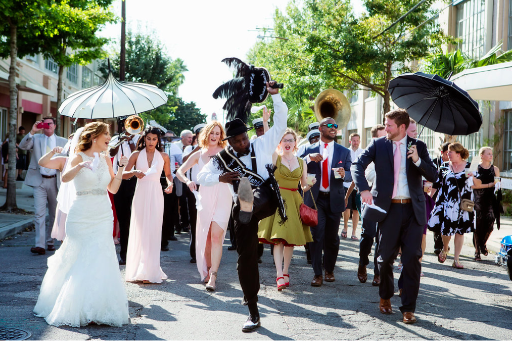 Leading the charge the second line band;  Kinfolk Brass Band , lead Ashley and Brian through the streets of New Orleans. A tradition, I personally had at my wedding, and wouldn't trade for the world! Ashley and Brian can feel the support of their family and friends behind them and start the celebration off with a bang! Captured By:  Becky Cooper Photography