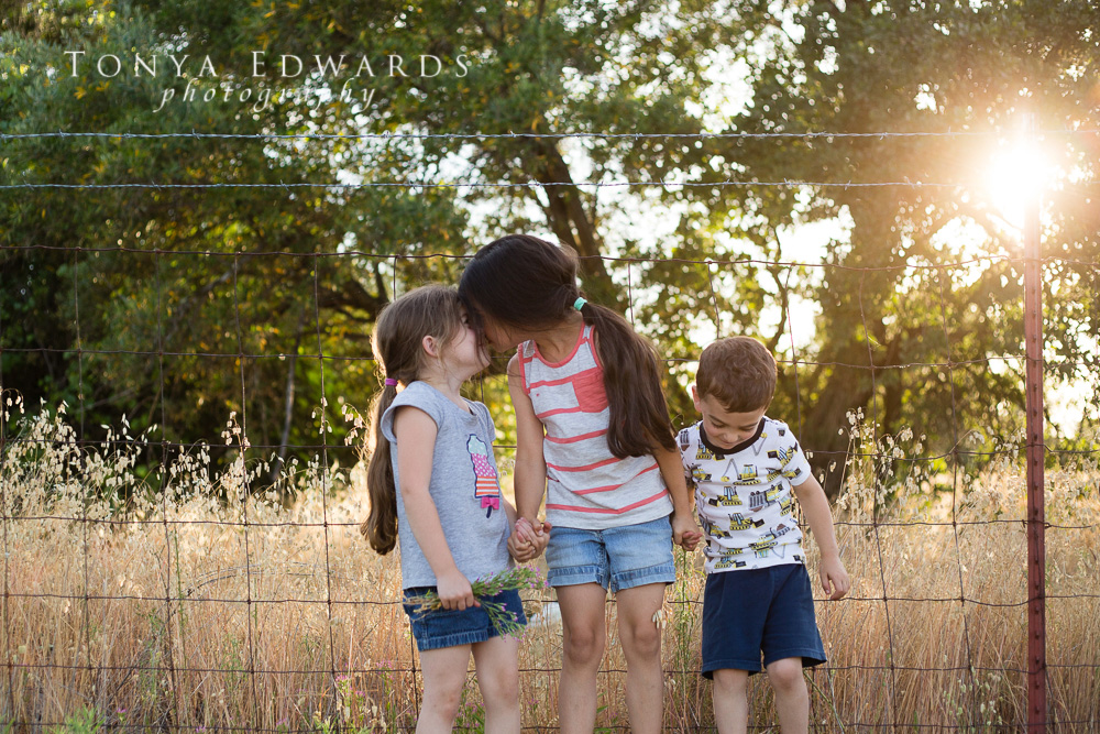 Tonya Edwards | Oroville Family Photographer | siblings in front of a fence at sunset