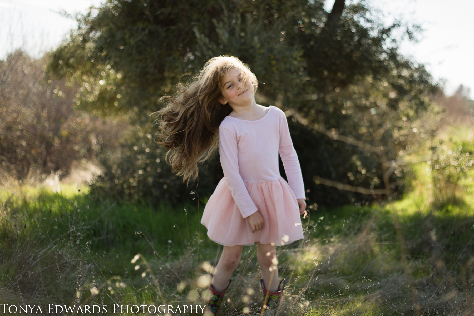 Tonya Edwards   Oroville Photographer   little girl in pink dress flipping her hair in a field with rim light
