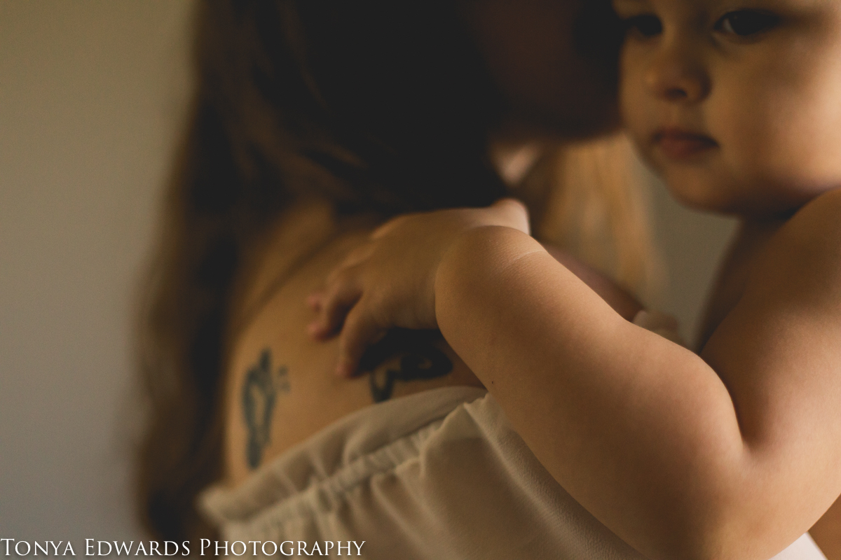 Tonya Edwards | Oroville Photographer | close up of baby girl hand on her mother's shoulder and mama kissing daughter