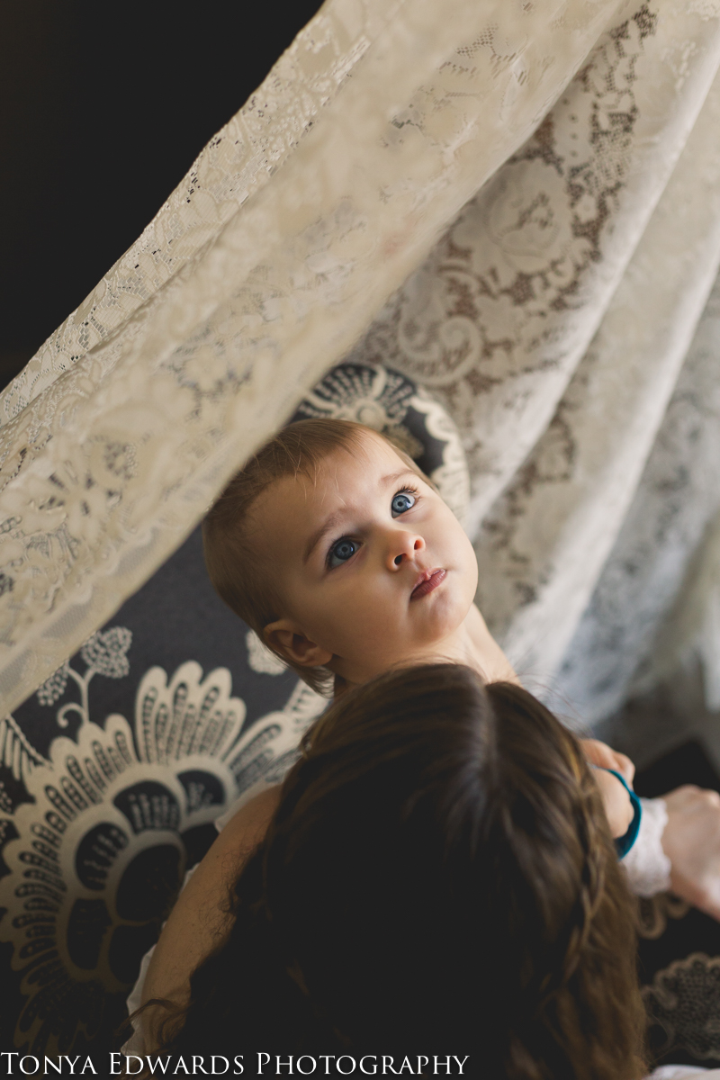 Tonya Edwards | Oroville Photographer | mother and daughter sitting in a chair looking out the window with lace curtains and blue eyes