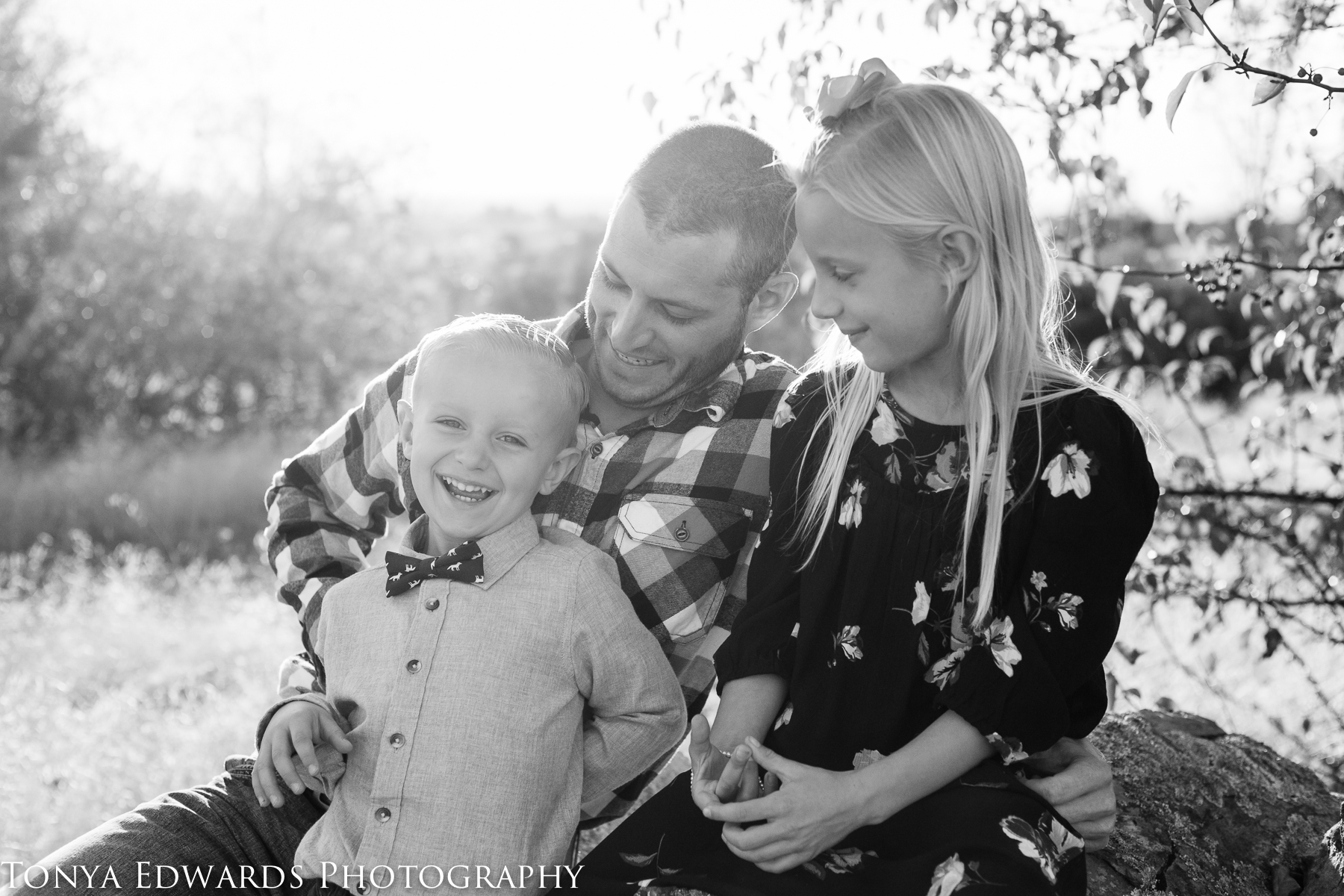 Tonya Edwards | Oroville Photographer | father and son and daughter playing laughing in black and white at golden hour