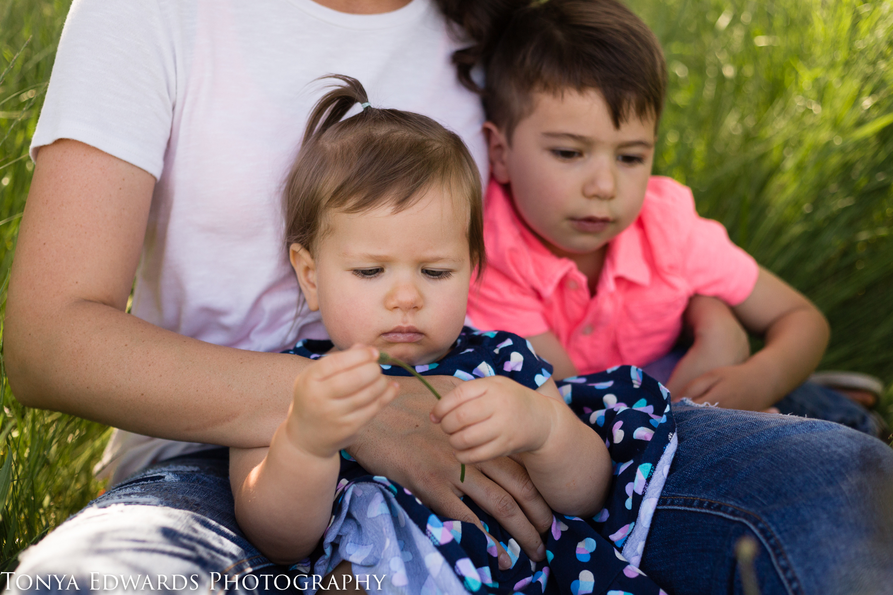 Tonya Edwards | Oroville Photographer | baby girl sitting with mama and brother picking grass at a mama and me mini session