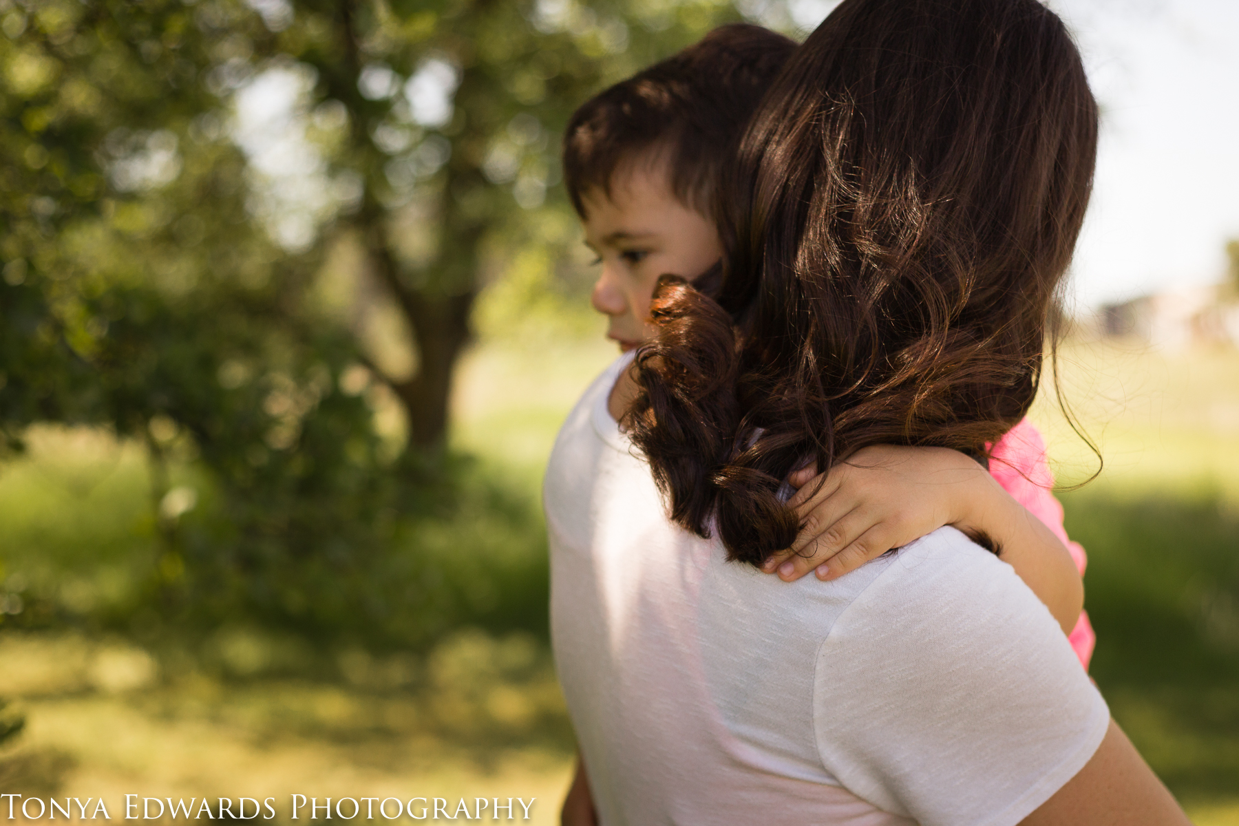 Tonya Edwards | Oroville Photographer | son hugging mother's neck while she carries him