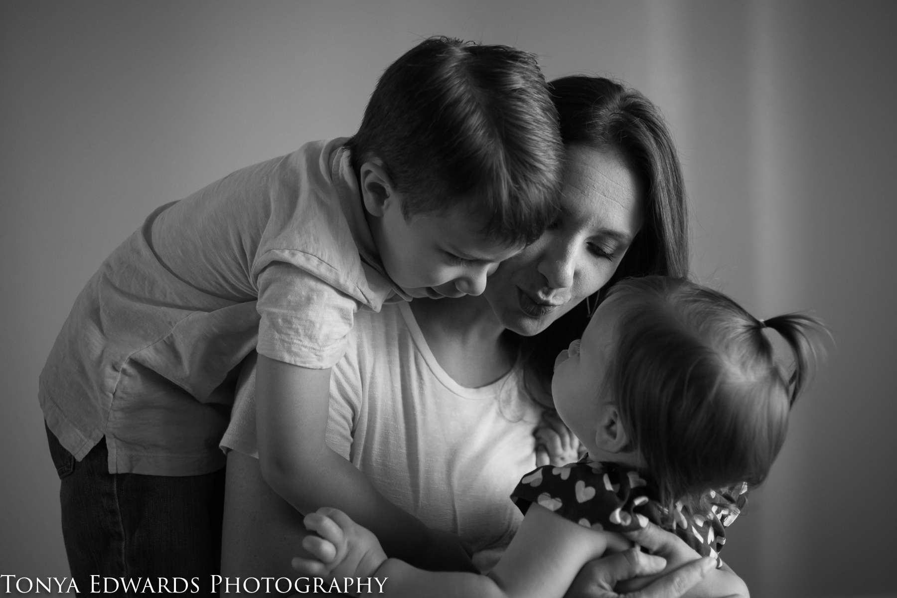 Tonya Edwards | Oroville Photographer | black and white photo of mother preschool boy and toddler girl blowing kisses