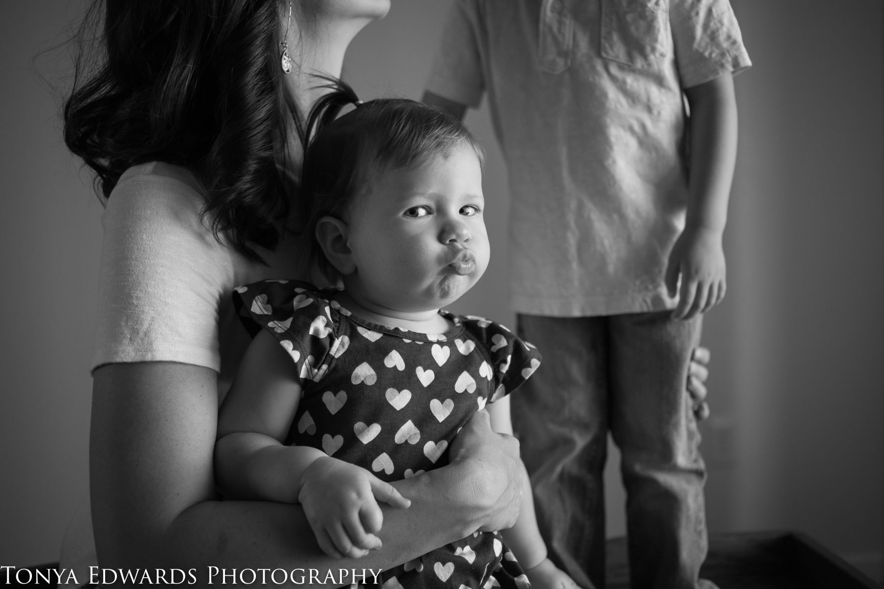 Tonya Edwards | Oroville Photographer | mommy and me mini session indoors window light in black and white mama son and baby daughter blowing kisses