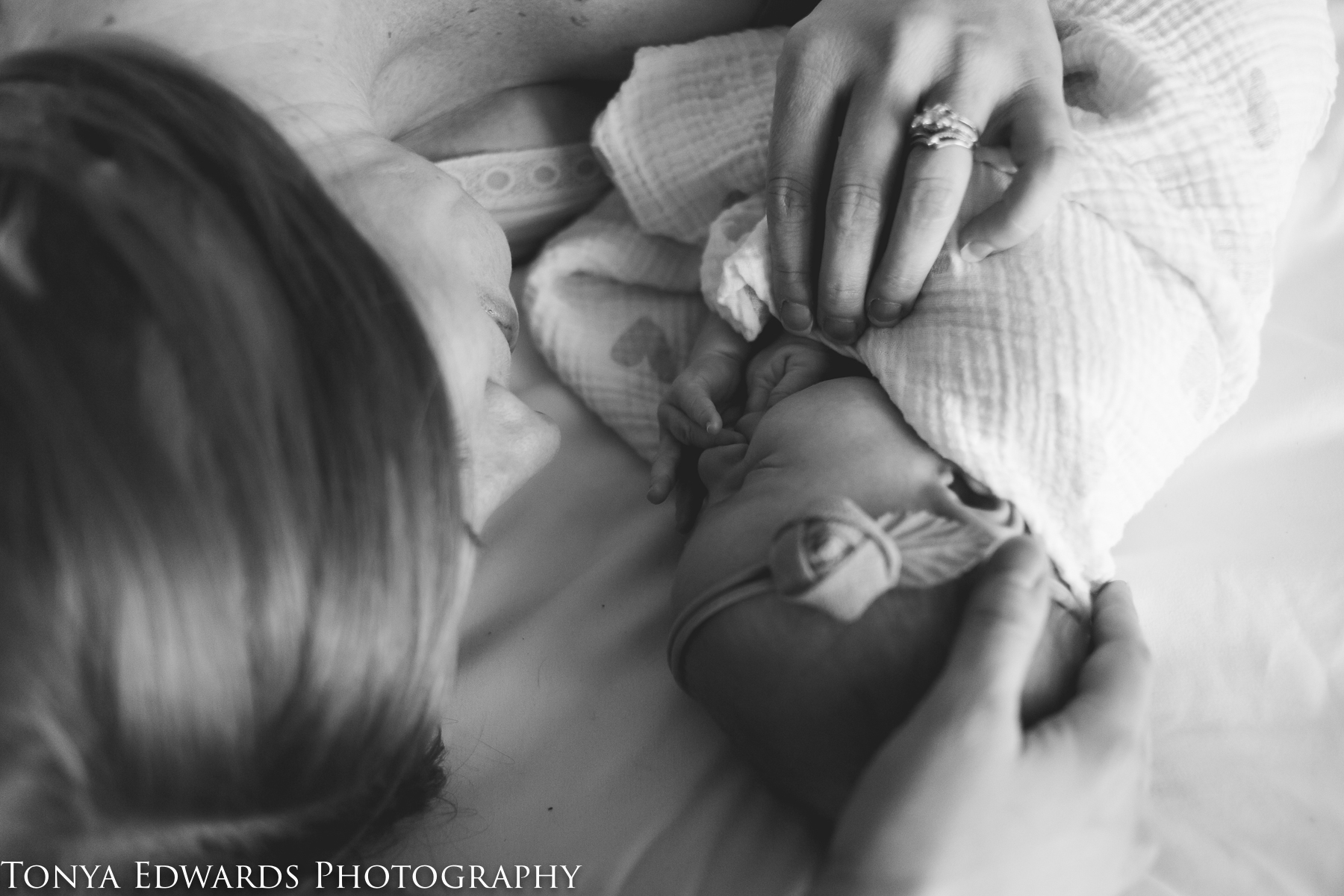 Tonya Edwards | Oroville Motherhood Photography | mother and baby daughter swaddled laying on a white sheet in soft window light