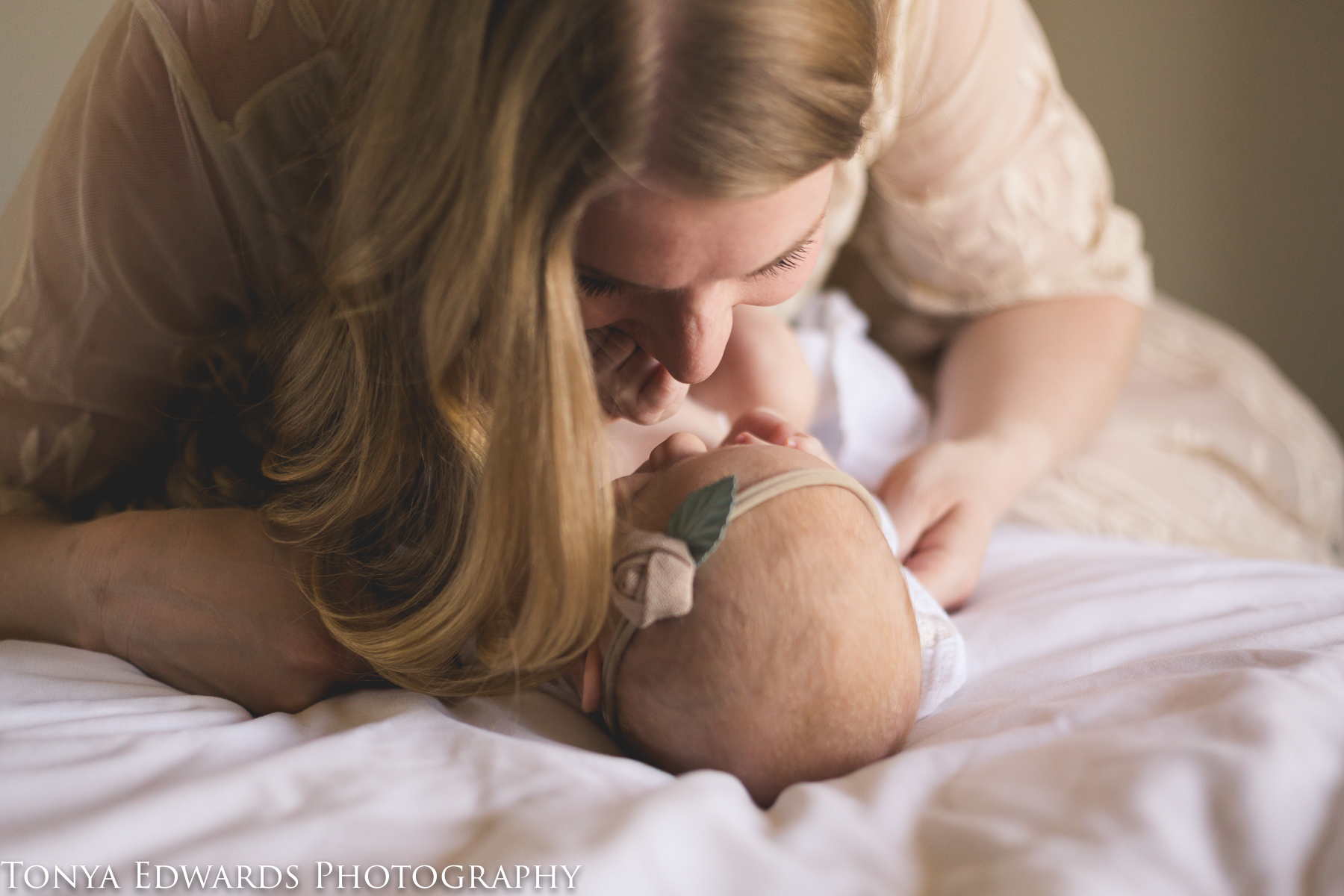 Tonya Edwards | Oroville Photographer | mother and baby mini session with infant girl laying on bed and mama kissing her nose