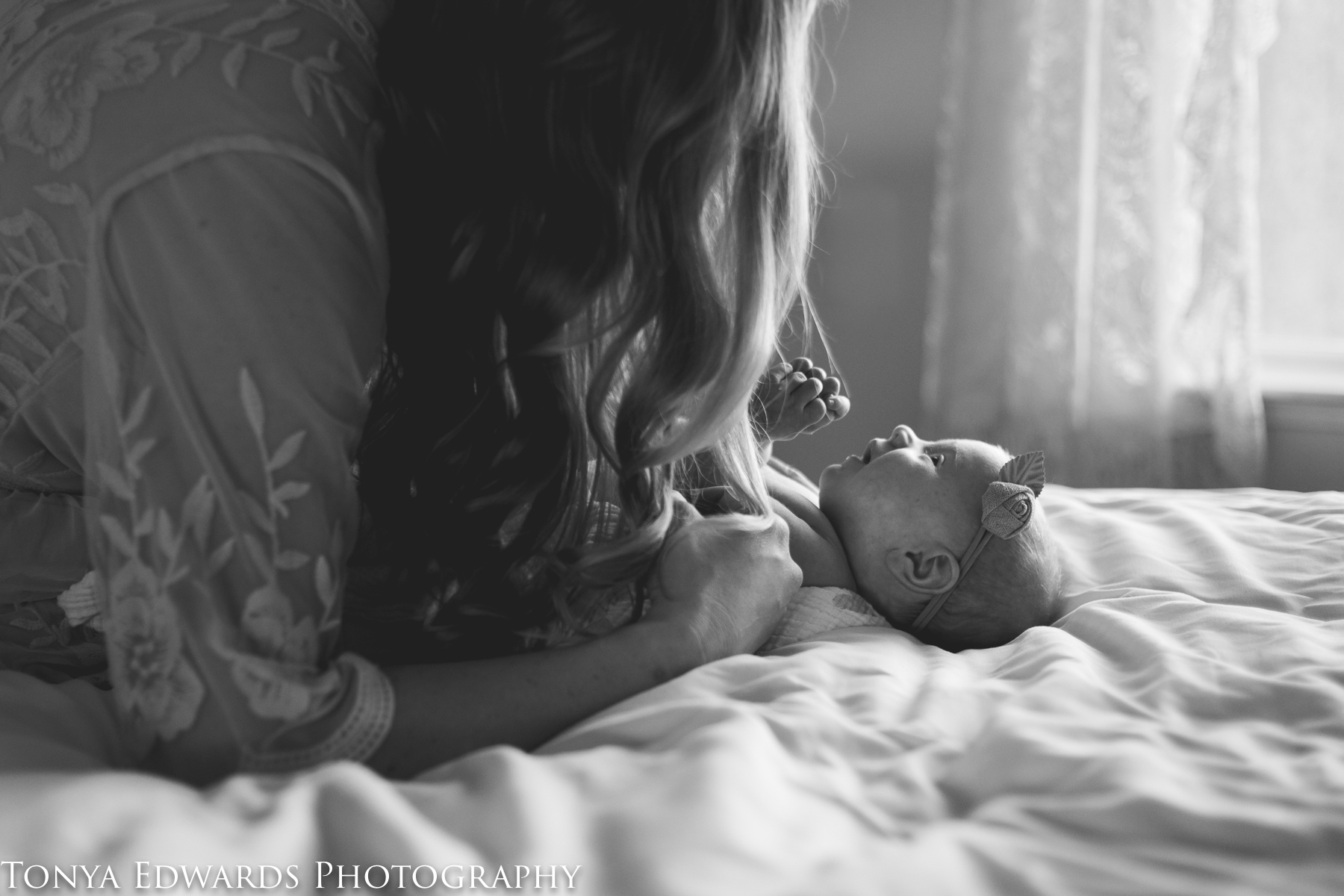 Tonya Edwards | Oroville Photographer | mother with long blond hair laying on bed playing with newborn baby girl in window backlight in black & white