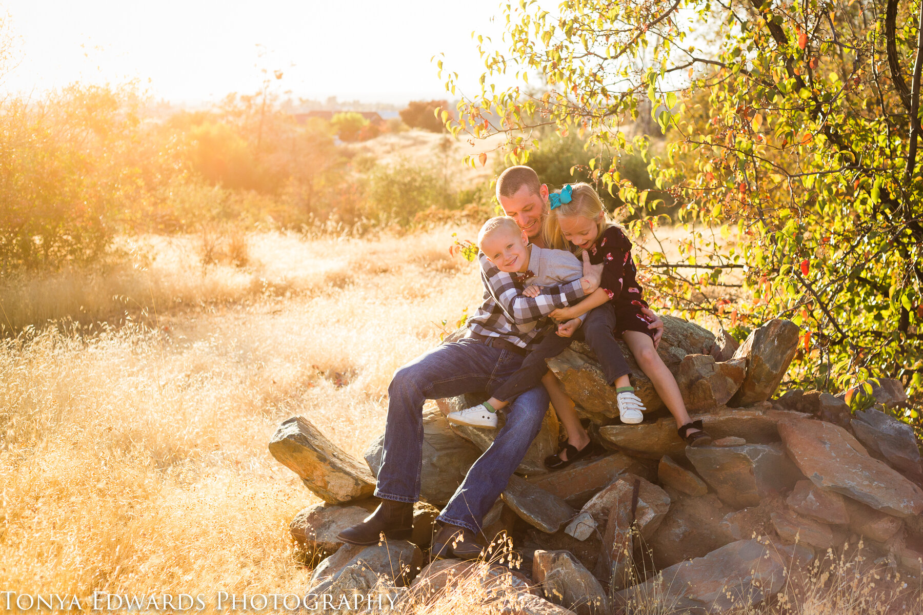 Tonya Edwards | Oroville Family Photographer | father and children sitting on a rock at sunset
