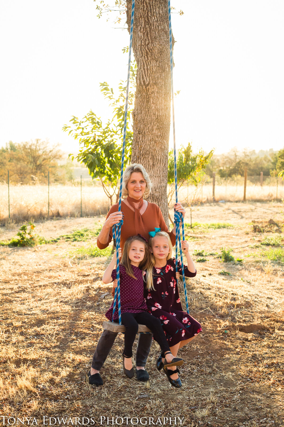 Tonya Edwards | Oroville Photographer | grandmother pushing granddaughters on swing golden hour