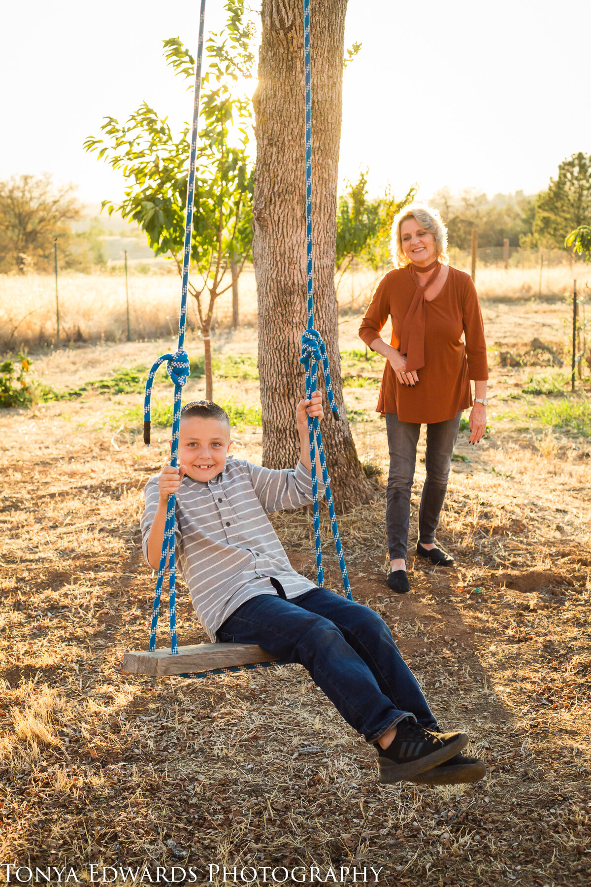 Tonya Edwards | Oroville Family Photographer | grandmother pushing grandson on tree swing during golden hour