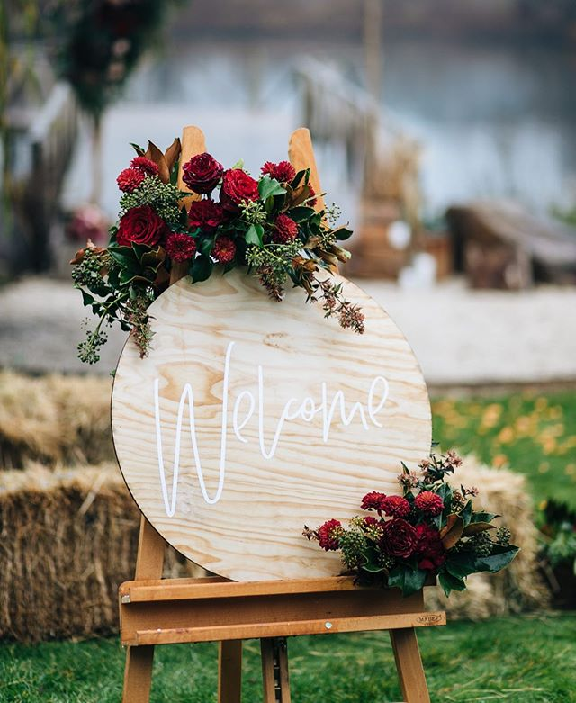 A little welcome styling by us,rich reds and lush foliage 🖤 . . . . . 📷 @melanie_kate_photography @stonesthrow_launceston  #adorneventstyling #weddinginspo #tasmania #weddingplanning #welcome #weddingwelcome #roundwelcomesign #weddingstyling #eventstyling #rusticwedding #countrywedding #wedspiration #weddingideas #eventinspo #weddingdeco #tasmanianweddingstylist