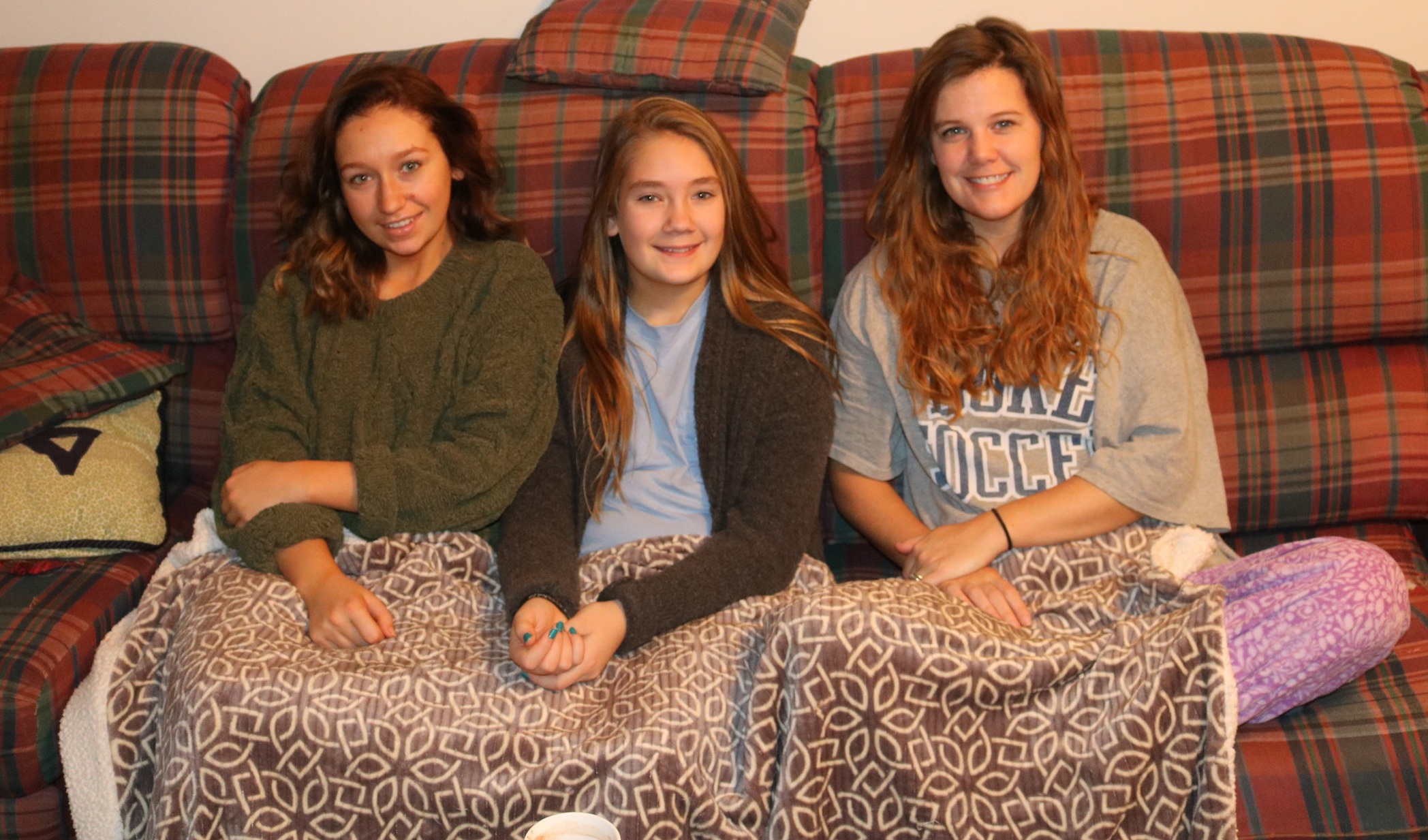 Maryellyn and the girls sharing the couch and a blanket on Christmas morning