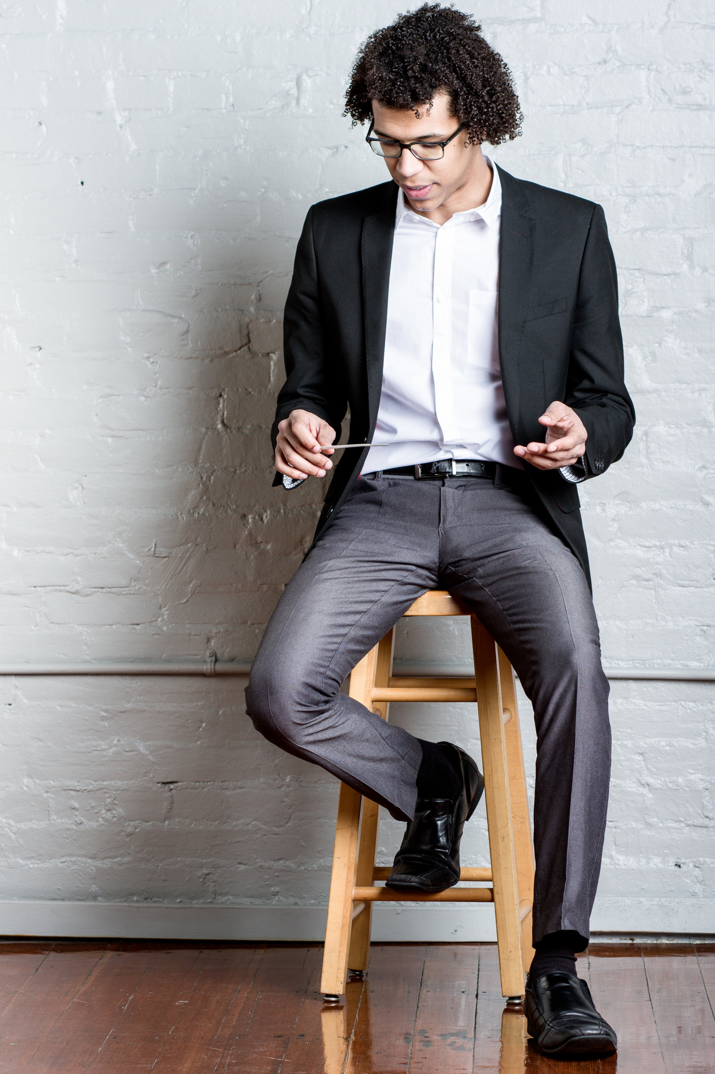 Jonathon Heyward conductor on stool looking down.jpg