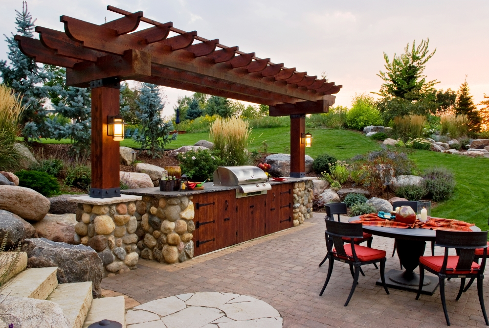 A beautiful sight as the sun sets near Victoria, MN. The outdoor kitchen overlooking a paved patio and natural stone seating gas fireplace.