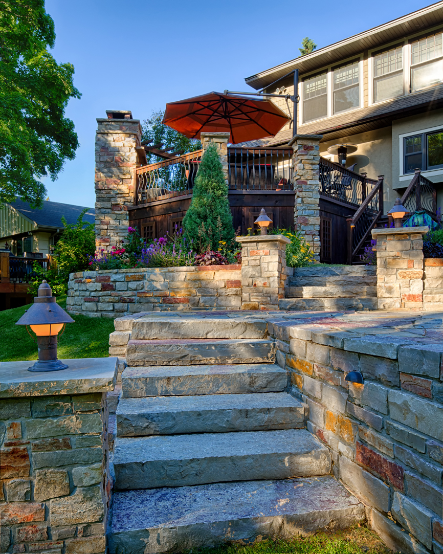 Edina homeowners love being outdoors, both with family and friends. Expanding their entertaining space to the deck and levels below include the patio, hot tub outdoor kitchen, fire pit and steps leading into the yard.