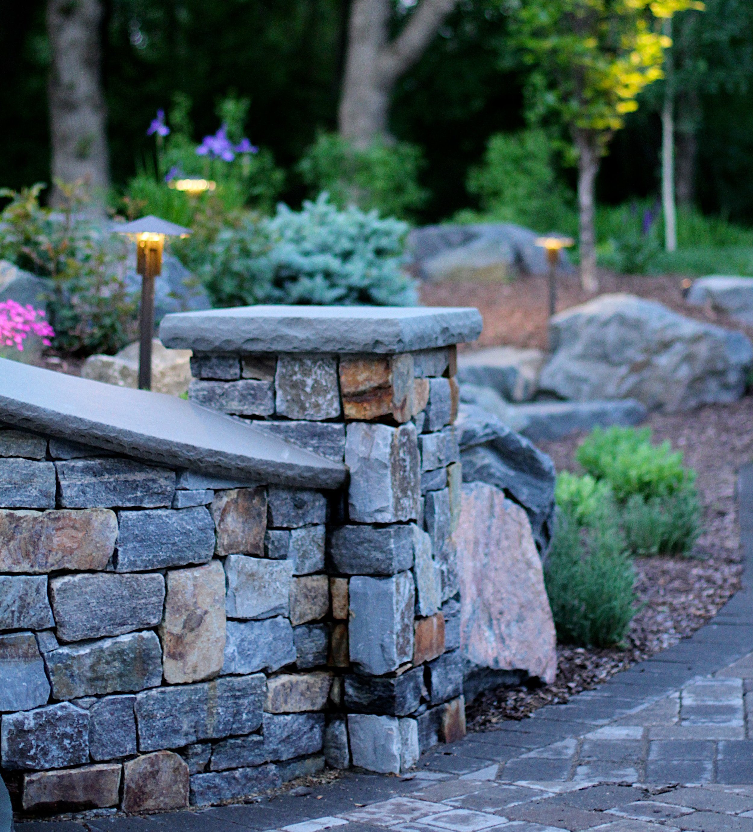 Curved natural stone handrail leading to curved walkway of Edina home entryway.