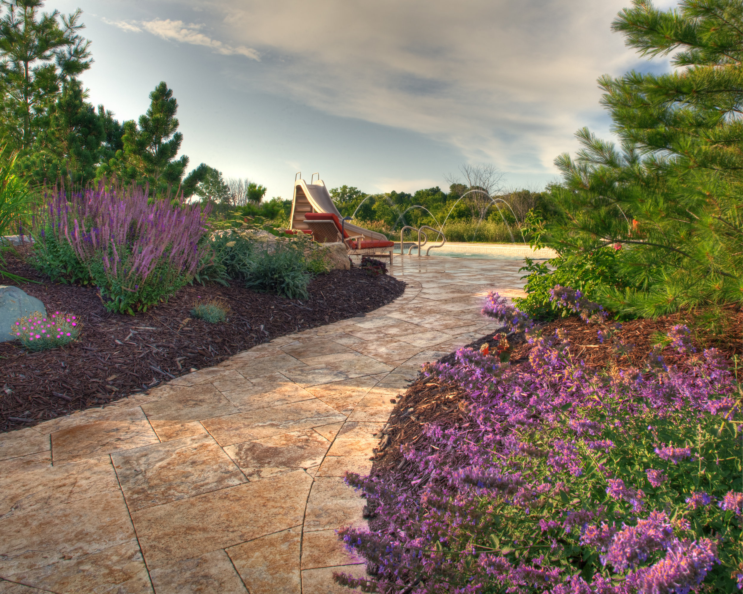 Walkway to Maple Grove area pool, surrounded by fresh smelling pines and salvia plants along the natural stone path.