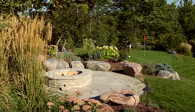 Excelsior backyard with gas fireplace and stone seats, overlooking a custom golf green.