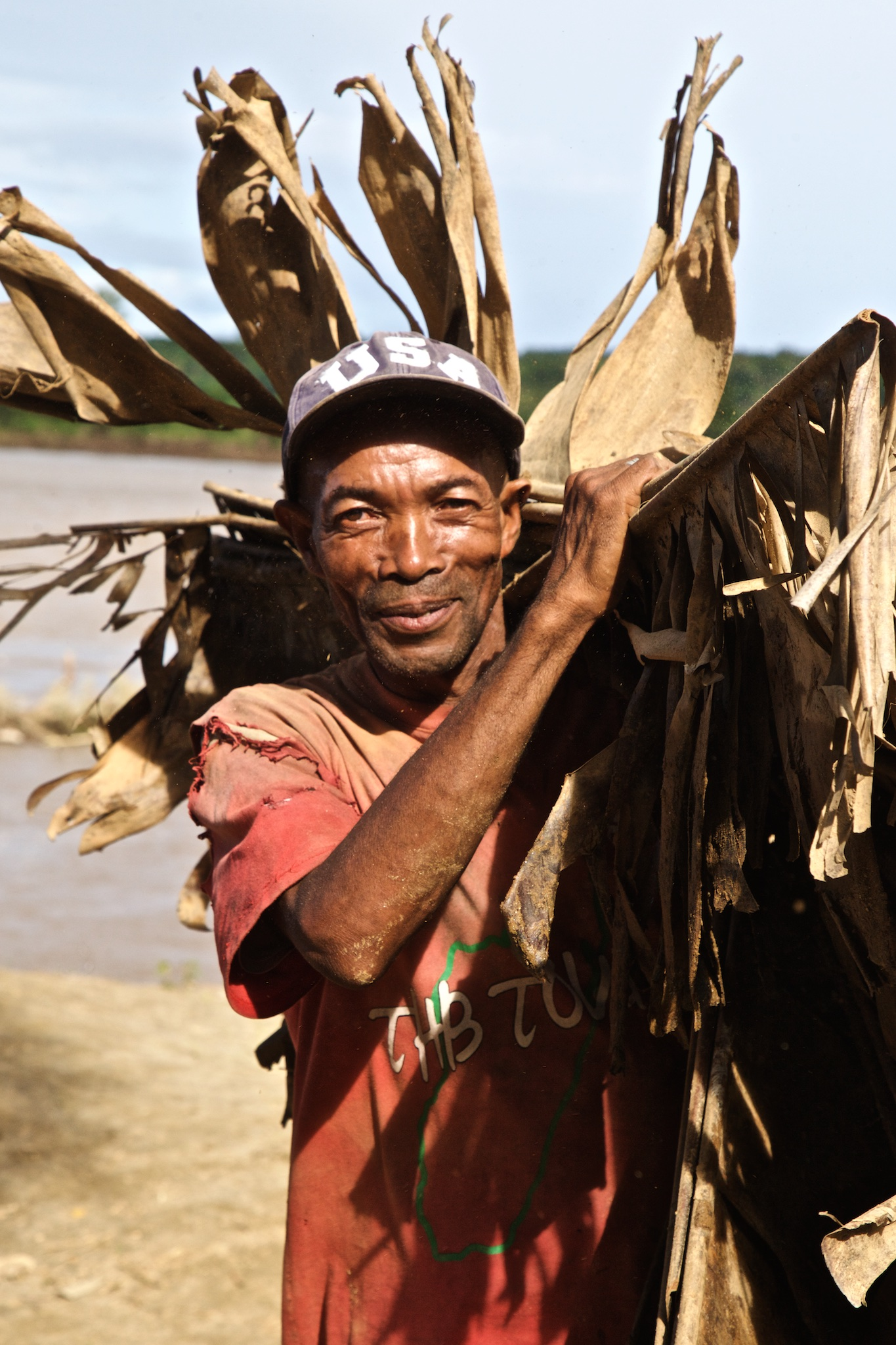 Liman Gathers Palm Fronds from the Riverbank. They Will Be Washed and Stacked to Thatch the New Homes
