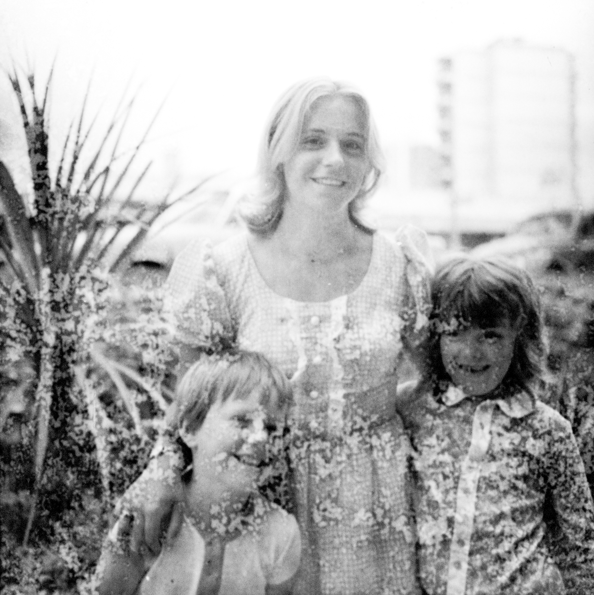 Image Description: What seems to be a family photo, we have a woman (possibly the mother), with two young boys. Boy (left) is smiling/laughing looking towards the camera, the woman (middle) is smiling casually looking towards the camera, with her hands around the young boys, and the second boy (right) is smiling wide looking to the left of the camera. Behind the people we have some bushed/plants, and behinds those in the distance there is cars, as well as a block of flats or offices on the far right.