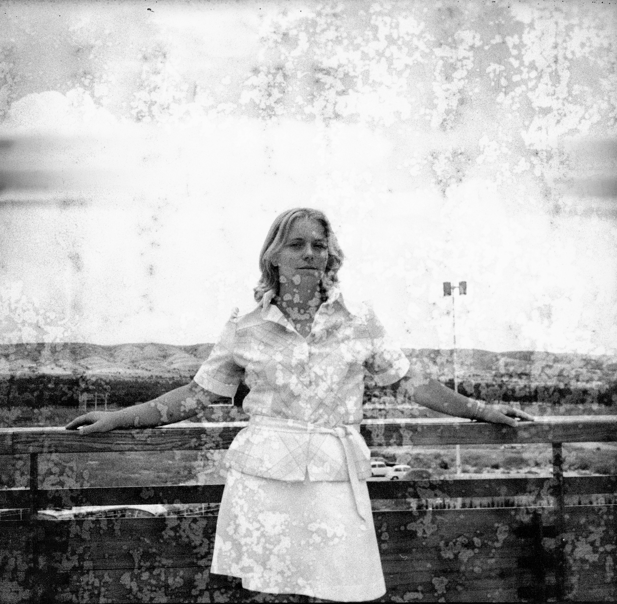 Image Description: In this image we have a teen or young adult stood in front of some fencing which is the same as the images with two young children (boy and girl) which are placed after photograph #3. The teen/young adult is leaning on the fencing, both her arms on either side placed on the top plank of the fence. She is wearing a white skirt, a light coloured plaid shirt with sleeves that end just before the elbow. The young lady has shoulder length light coloured hair. Not much scene in this photograph, except for sky, some green-land, a car park and the fencing behind her.
