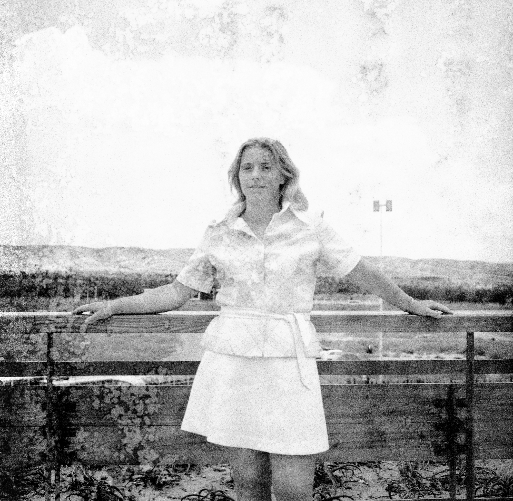 Image Description: In this image, which is similar to the one above, we have a teen or young adult stood in front of some fencing which is the same as the images with two young children (boy and girl) which are placed after this photograph. The teen/young adult is leaning on the fencing, both her arms on either side placed on the top plank of the fence. She is wearing a white skirt, a light coloured plaid shirt with sleeves that end just before the elbow. The young lady has shoulder length light coloured hair. Not much scene in this photograph, except for sky, some green-land, a car park and the fencing behind her.