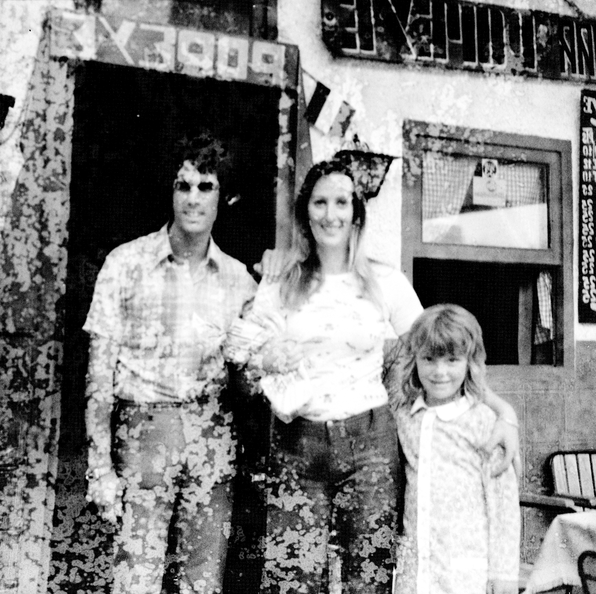 Image Description: Another family photograph, featuring three different people. In this photograph we have a man (far left), a woman (center), and a young boy (far right). The man is wearing a light, multi-toned plaid shirt, light coloured trousers/jeans, sunglasses and watch on his right wrist. He has dark curly hair, which cannot be seen in great deal due to the quality of the negative image. His hand is leaning on the woman's right shoulder. The woman, is about an inch smaller than the man, and is wearing some sort of patterned t-shirt, and dark grey trousers. She has what looks like a loaf of bread in her right arm, carrying it like you would a small child. Her left arm is around the young boy. The young boy is small, he is wearing a white patterned shirt. His hair shoulder length. They are all smiling, looking towards the camera. They are stood in front of, what seems to be a small store or cafe. To the far right, going of the image are chairs and the start of a table - these are placed under a window of the store or cafe.