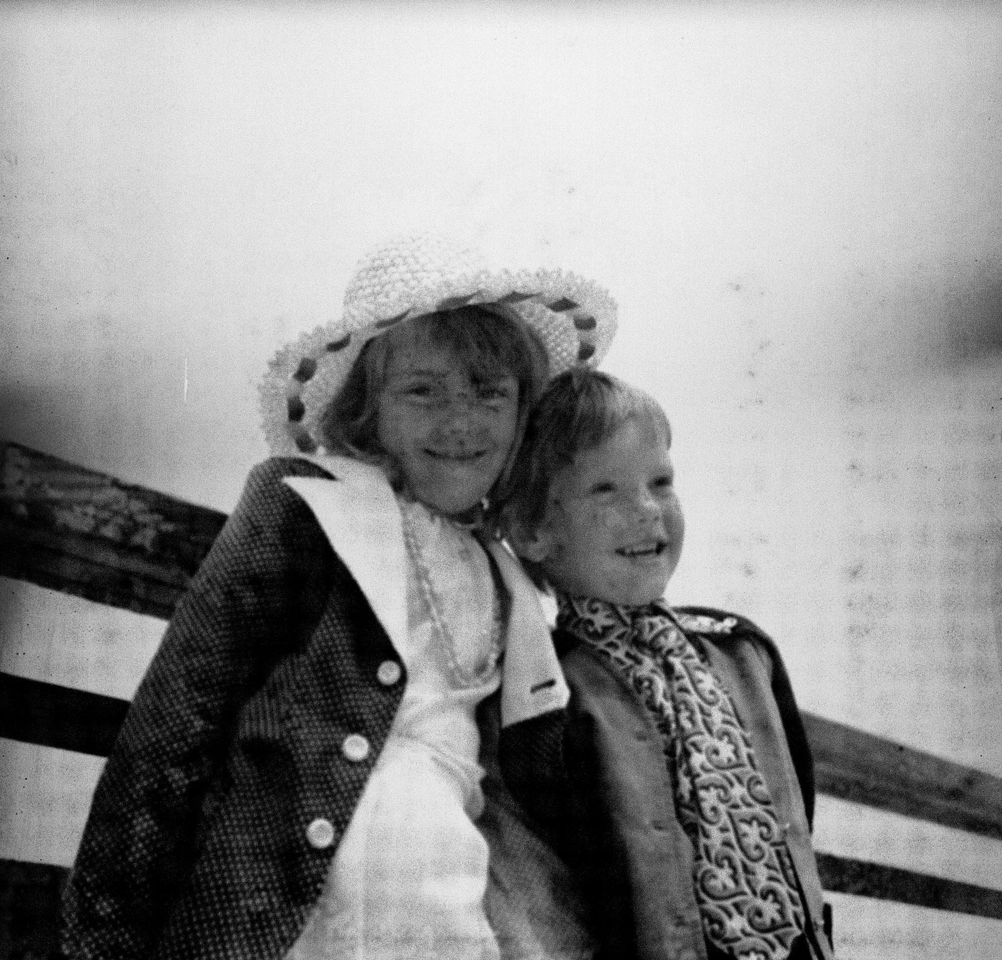 Image Description: Photograph features a young boy and a girl. The girl (left) is wearing sun hat, her hair down, with a white dress, what seems to be pearls around her neck, and a white and grey jacket. The boy (right) is wearing a black and grey jacket, a patterned scarf with trousers and white suspenders that can't be clearly seen the photograph. The girl is looking at the camera smiling, whilst the boy is looking straight ahead of him (to our right), again smiling wide.  Not much scene in this photograph, except for sky and one plank of fencing behind them, which they seem to be leaning on