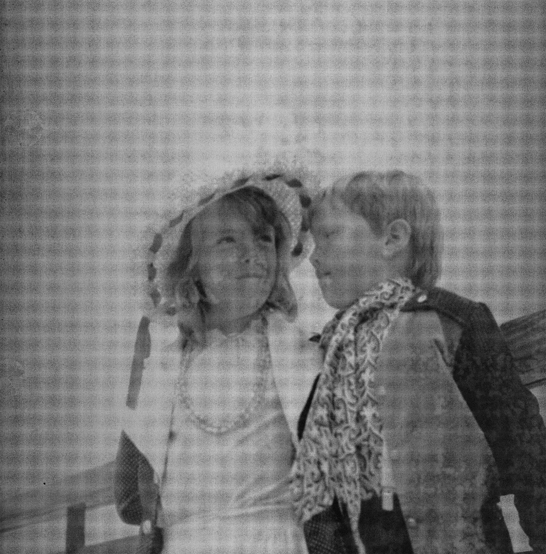 Image Description: Photograph features a young boy and a girl. The girl (left) is wearing sun hat, her hair down, with a white dress, what seems to be pearls around her neck, and a white and grey jacket. The boy (right) is wearing a black and grey jacket, a patterned scarf with trousers and white suspenders that can't be clearly seen the photograph. The girl is looking just past the boy in the image to her left (our right), looking into the distance, possibly at someone else whilst the boy is looking at the girl. Not much scene in this photograph, except for sky and one plank of fencing behind them, which they seem to be leaning on.
