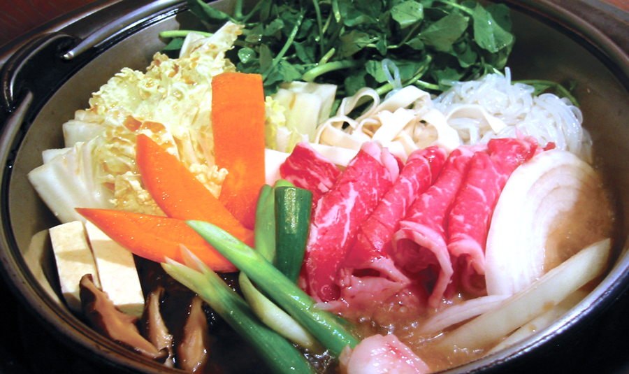 Sukiyaki - すき焼きis a slow-simmering, sweet, smooth, and silky mix of fresh meats and vegetables, all cooked at your table in a shallow iron pot. The marinade is a mixture of soy sauce, sugar, and mirin rice vinegar.The ingredients caramelize and bathe in the mixture, then are usually dipped in a small bowl of raw egg.