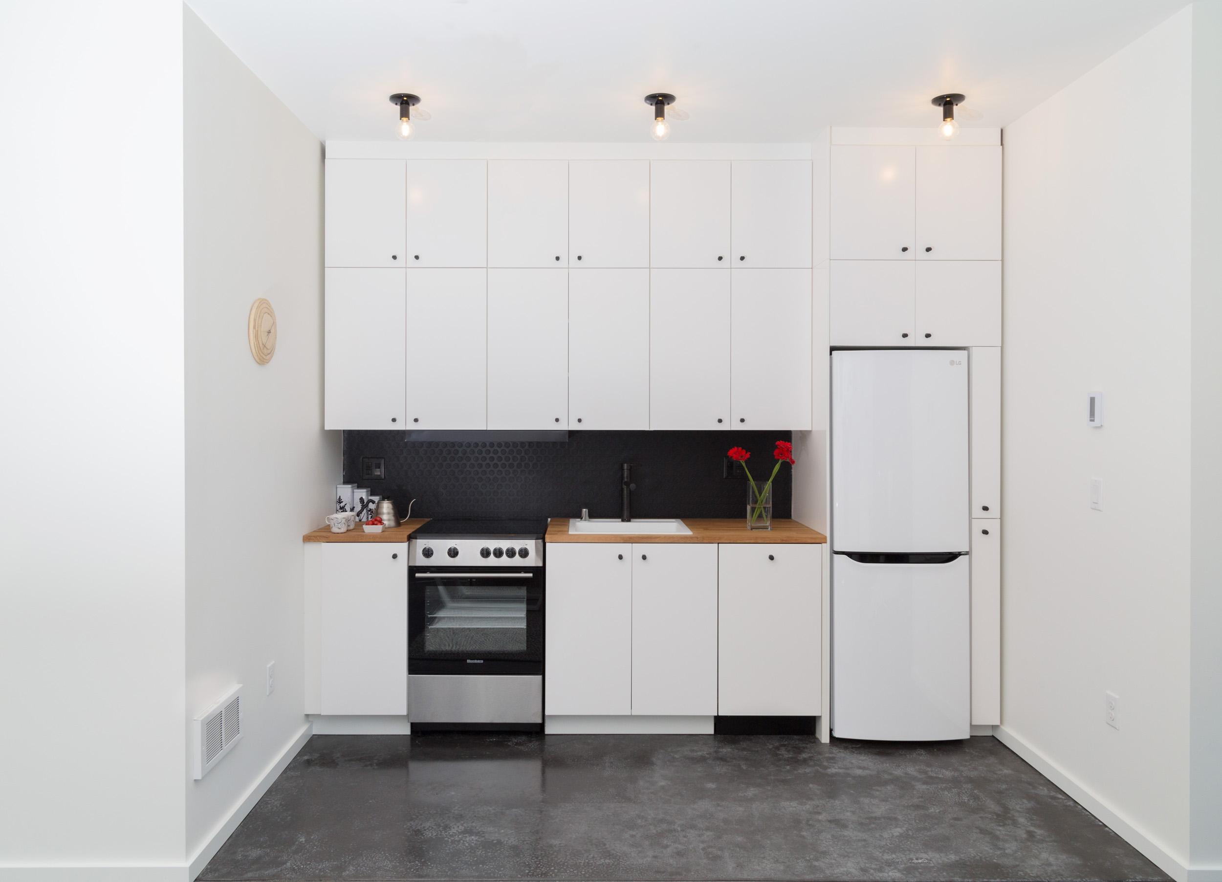 WC-STUDIO-PROSPECT-KITCHEN-WHITE-CABINETS-BLACK-CONCRETE-FLOORS-BUTCHER-BLOCK-COUNTERTOP.jpg