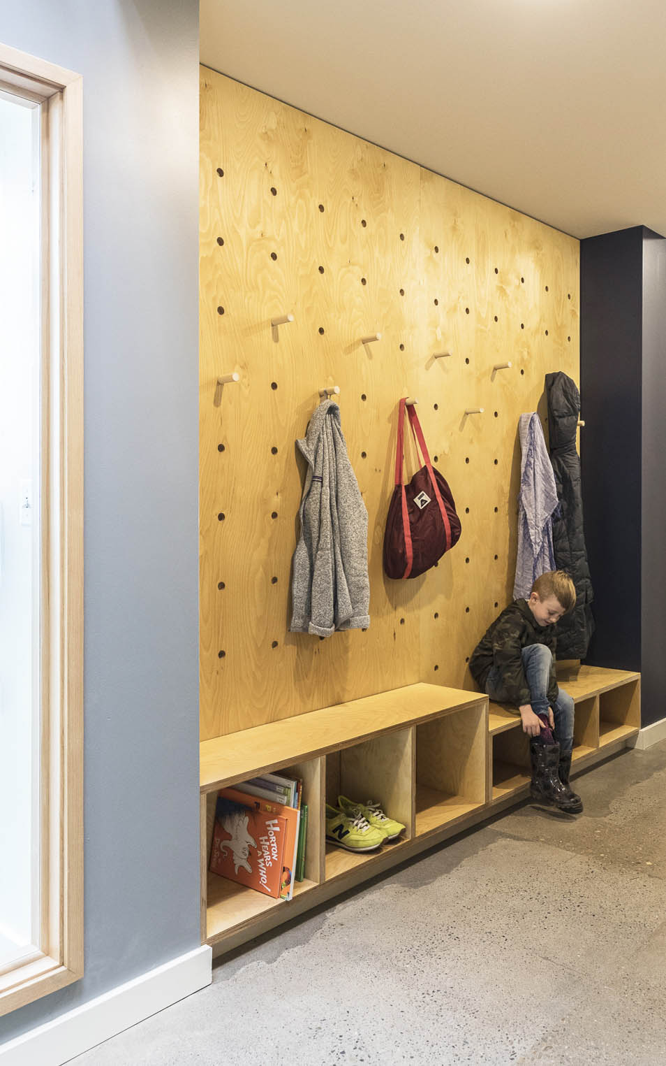 An oversized pegboard, bench and cubbies create a place for boots, coats and bags. Logo below by Caitlin Dale.