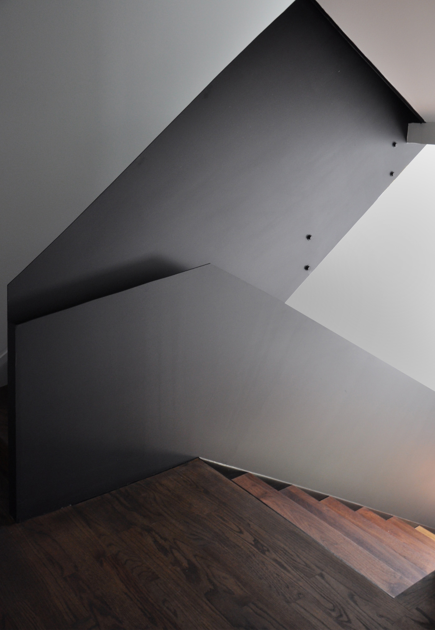 Walnut flooring and stair treads complement the powder-coated steel railing