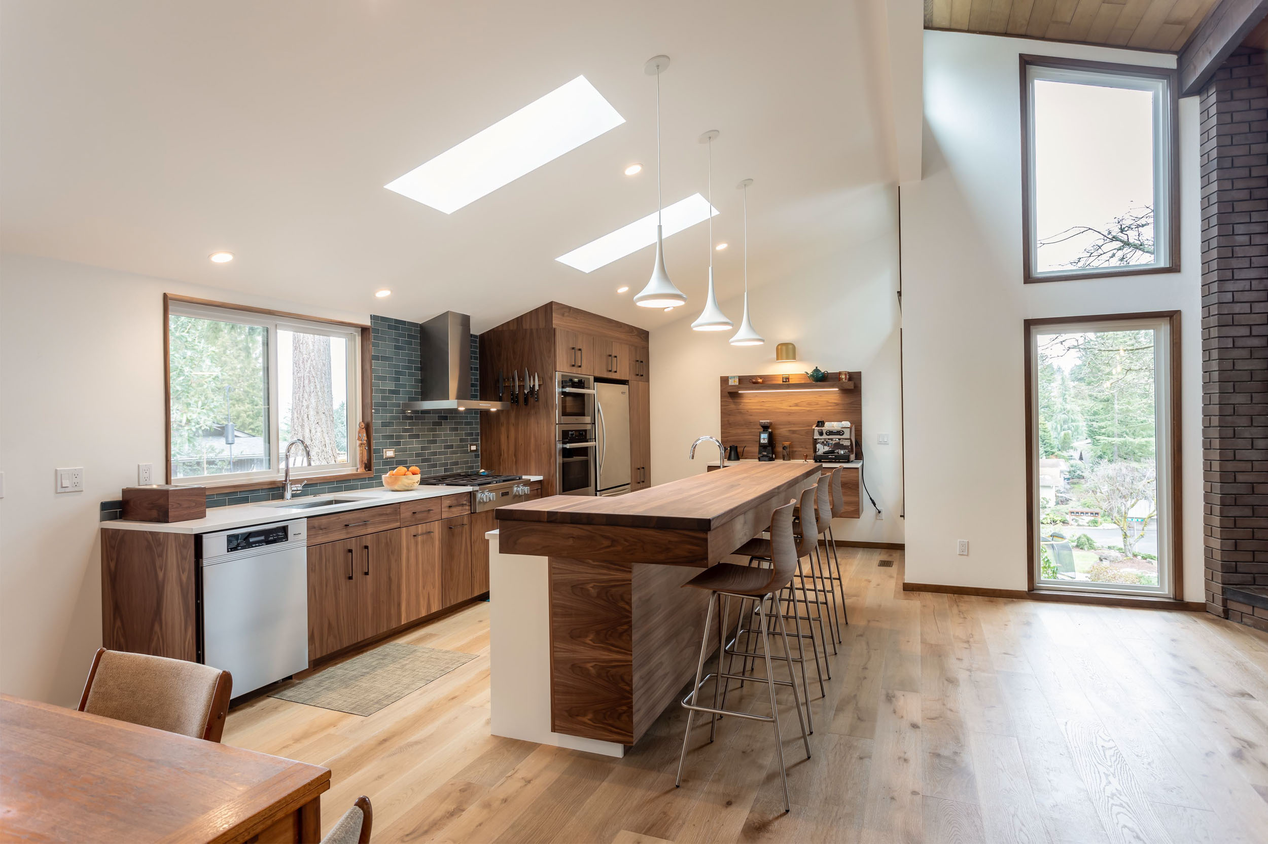 The walnut flooring, cabinet faces and Boos Block island stands out against the white countertops and walls.