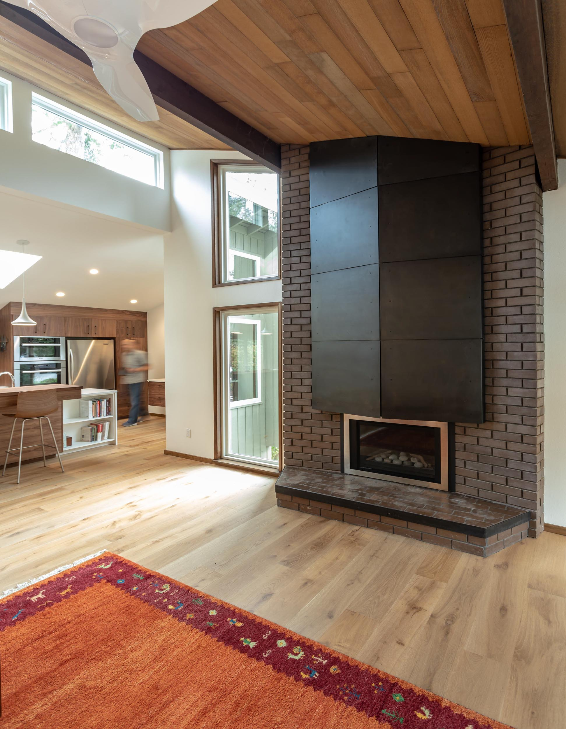 """The original hearth was covered with wood shingles, something the owners were not excited about. They were looking for a contemporary upgrade. We worked together with a steel fabricator to install 1/8"""" steel panels with a gun metal finish."""