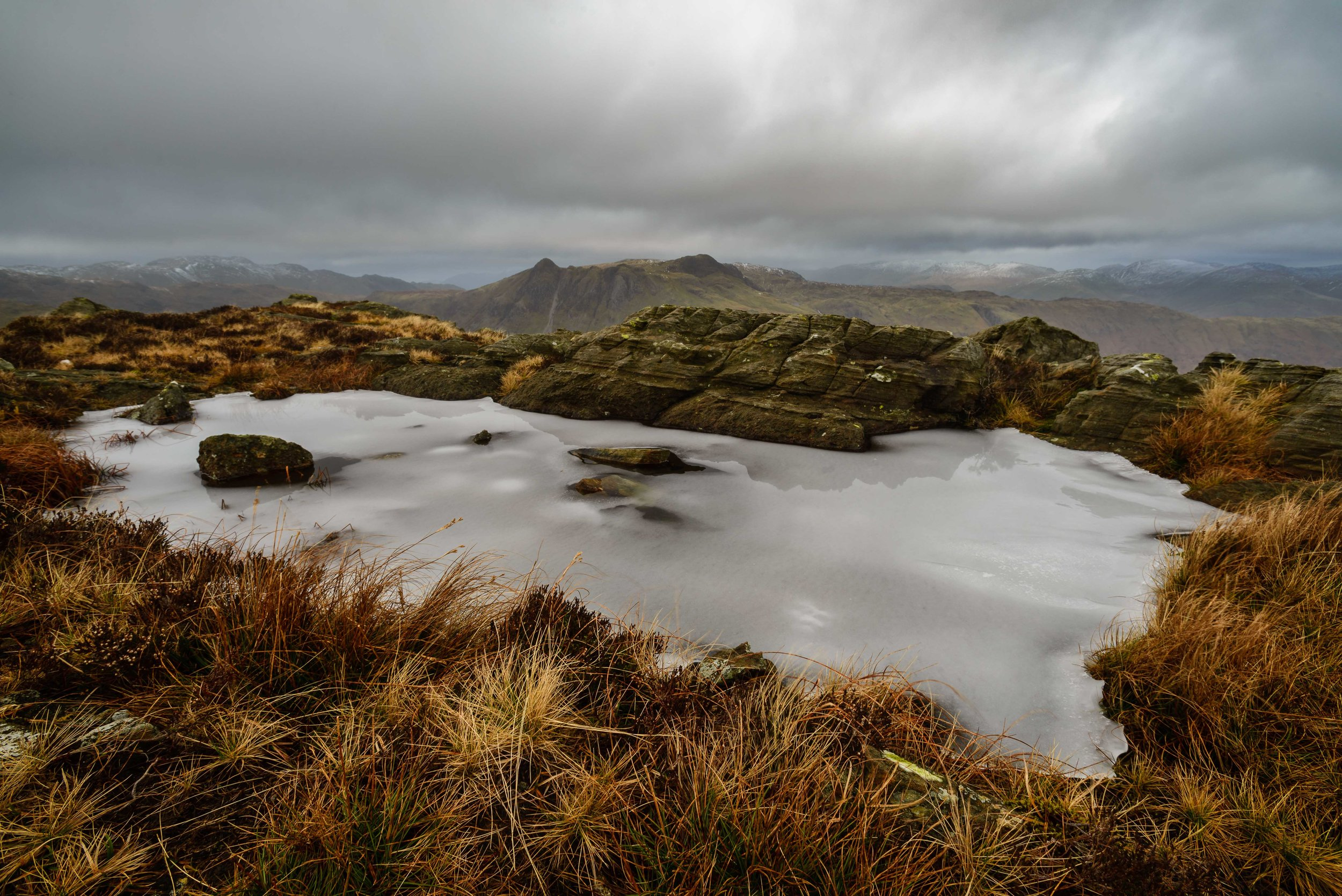 Tiny frozen tarn with the Langdales in the background.