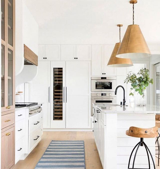 We love this look! The two toned cabinets are so beautiful paired with those gold drum pendants! So well done,  @briahammelinteriors