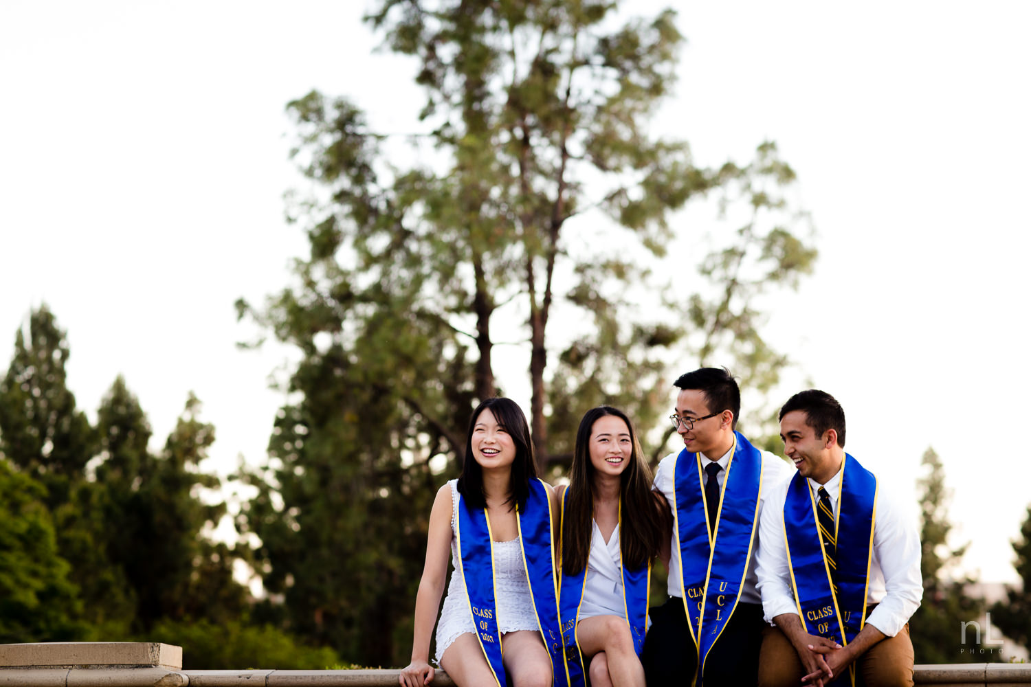 los angeles ucla senior graduation group portrait of best friends in white laughing while sitting on royce quad balcony