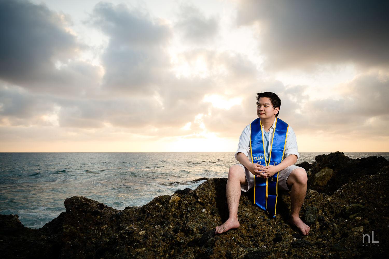 los angeles ucla senior graduation epic portrait guy sitting on rock newport beach at sunset