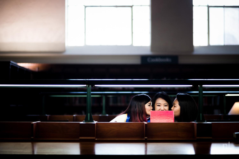 los angeles ucla senior graduation portrait cute best friends girls kissing cheeks in powell library