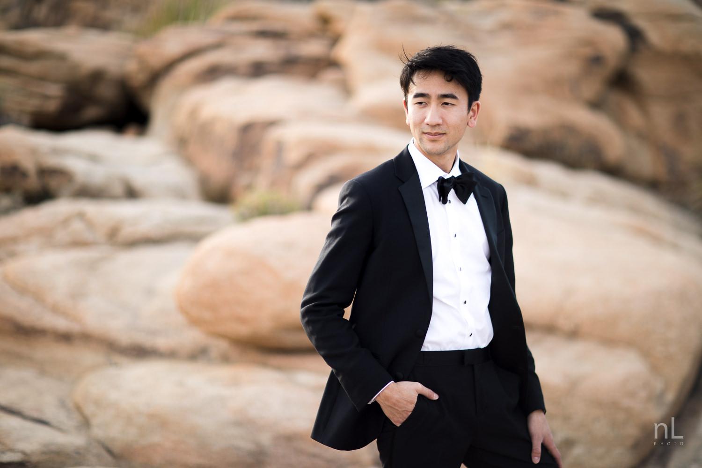 joshua-tree-engagement-wedding-elopement-photography-stylized-photoshoot-groom-in-tuxedo-standing-on-rocks